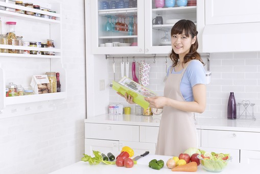 キッチンでレシピを見る女性