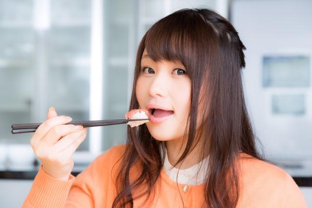 一口サイズのお寿司を頬張る女性